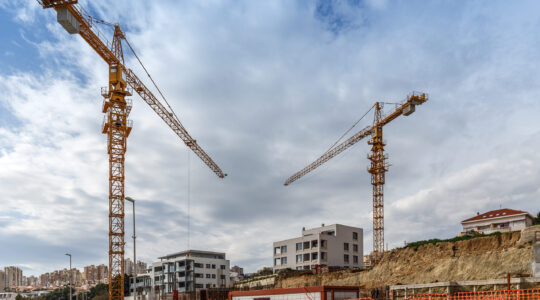 Construction site background. Hoisting cranes and new multi-storey buildings