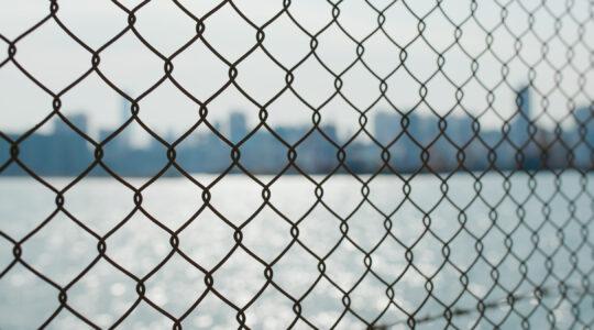 Metallic fencing at seaside in evening
